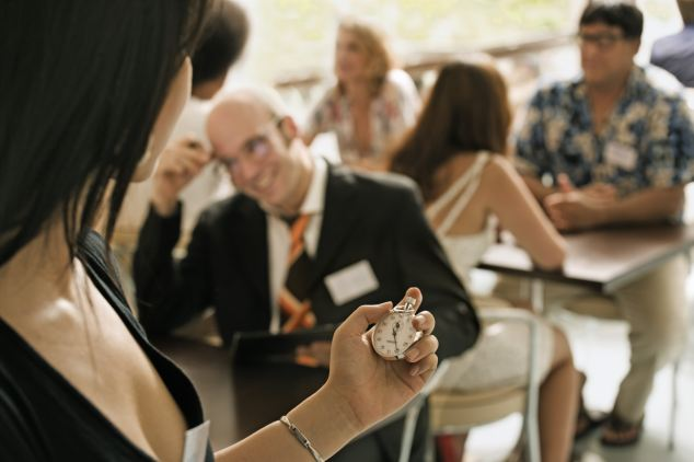 Woman Timing Speed Dating Event --- Image by © sven hagolani/Corbis