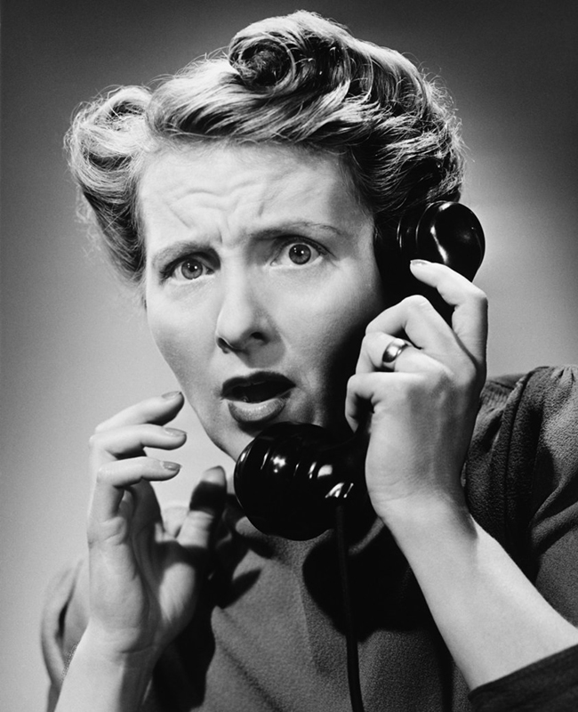 Terrified woman talking on phone, (B&W), portrait